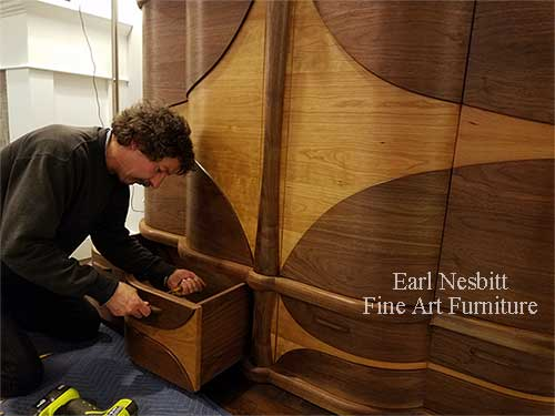 Earl attaches pull to a drawer of a custom made art deco cabinet