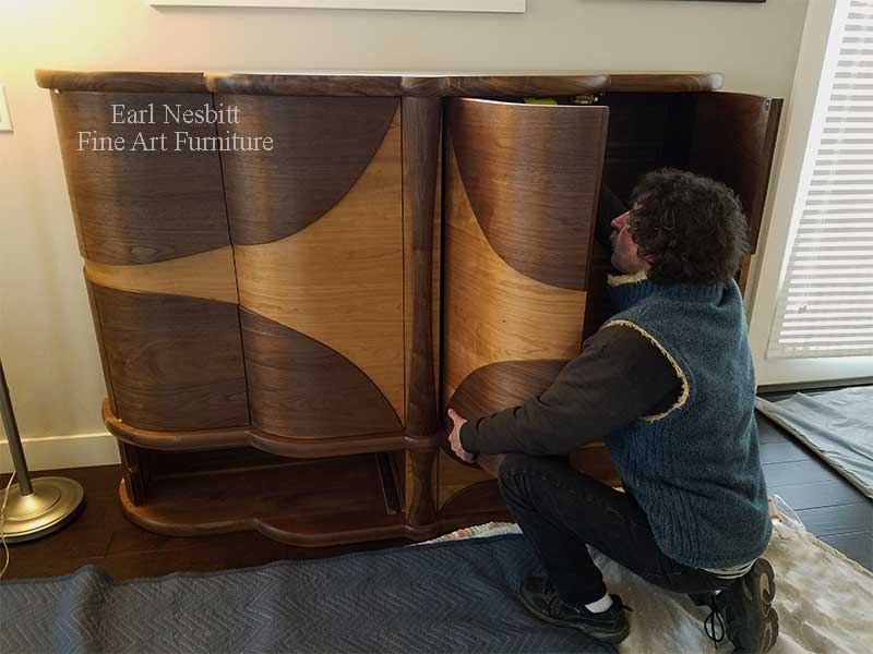Earl installing retractable doors on a custom made art deco cabinet