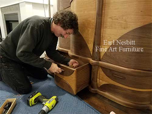 Earl attaches a pull on a drawer of a custom made art deco cabinet