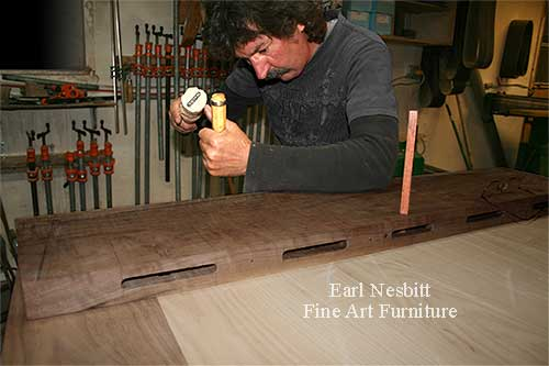 Earl pegging tenons at the end of a custom made dining table showing mortises