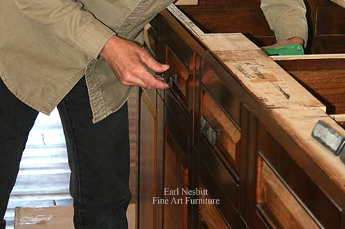 Earl placing pulls on a custom made cabinet