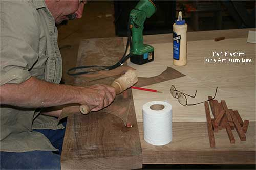 Earl pegging tenons at the end of a custom made dining table