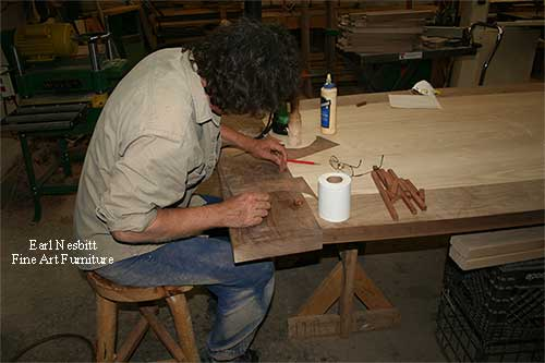 Earl pegging tenons at one end of custom made dining table