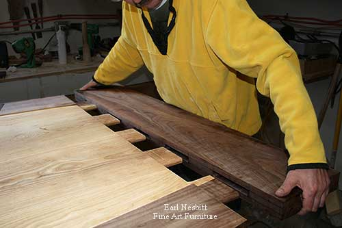 Earl inserts mortise and tenon ends of a custom made dining table, and Earl pegs tenon