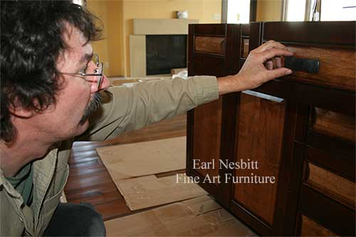 Earl checks drawer pull of custom made cabinets