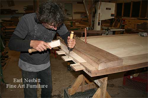 Earl pegging tenons at the end of a custom made dining table showing tenons