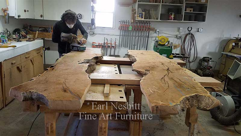 Earl leveling mesquite slabs for a custom made live edge dining table with eight chairs