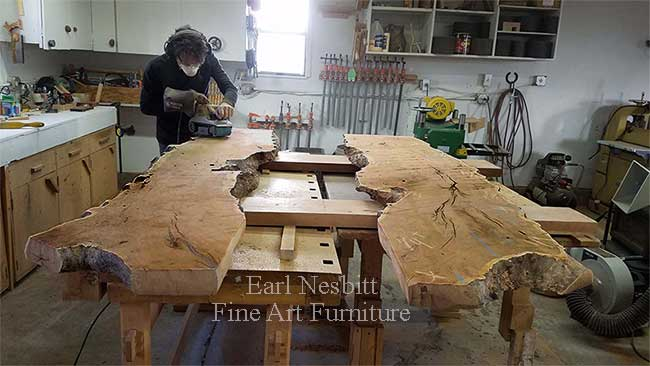 Earl rough sanding mesquite slabs for a custom made live edge dining table with eight chairs