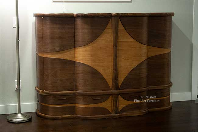 art deco bar cabinet emphasizing curved design from one side with all doors and drawers closed